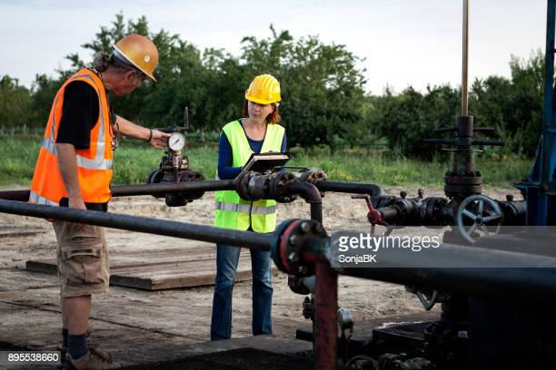 two engineers at oil field - pressure gauge stock photos and pictures
