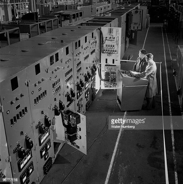 Two engineers at the English Electric plant in LIverpool examine a switchgear panel destined for Calder Hall nuclear power station in Cumbria English...