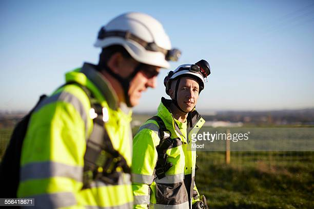 two engineers at wind farm, walking together - helmet stock pictures, royalty-free photos & images