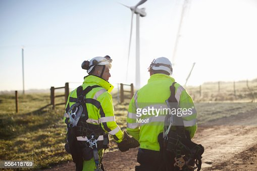 Two engineers at wind farm, walking together, rear view