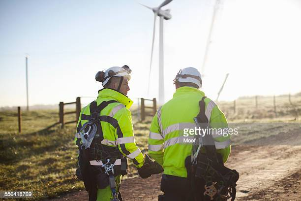 two engineers at wind farm, walking together, rear view - windenergie stockfoto's en -beelden