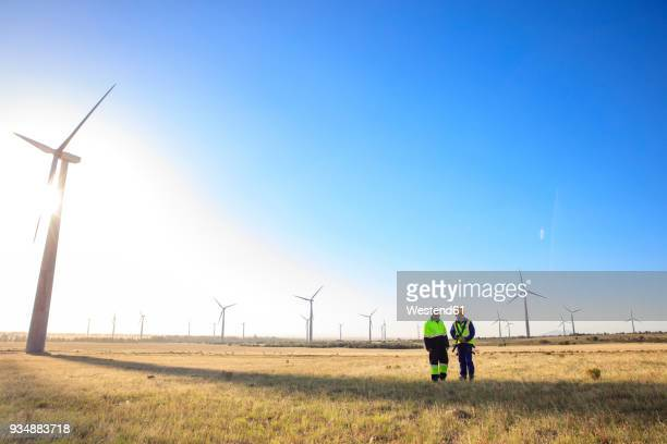 two engineers discussing on a wind farm - windmills stock photos and pictures