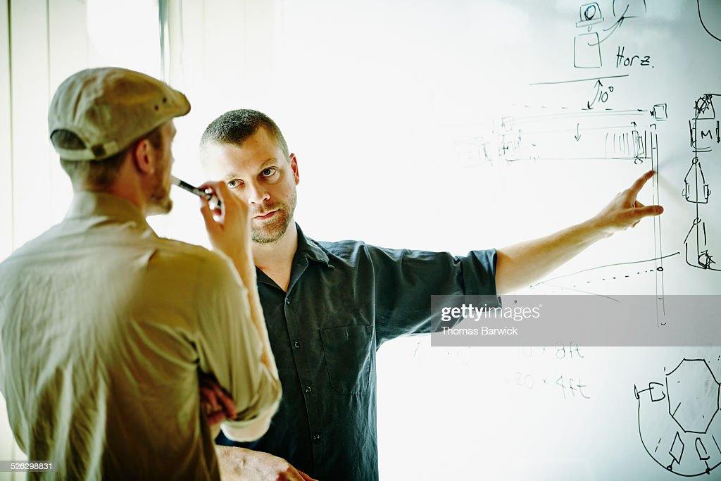 Two engineers discussing project design in office : Stock Photo