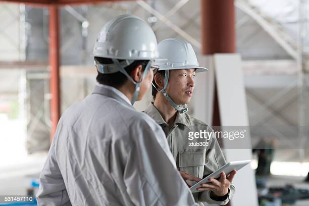 Two engineers discussing while using a digital tablet