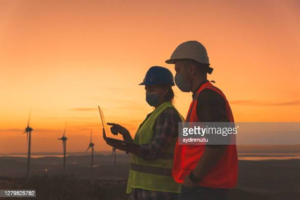 two engineers doing laptop inspections at the wind turbine field, face masks - power occupation stock pictures, royalty-free photos & images