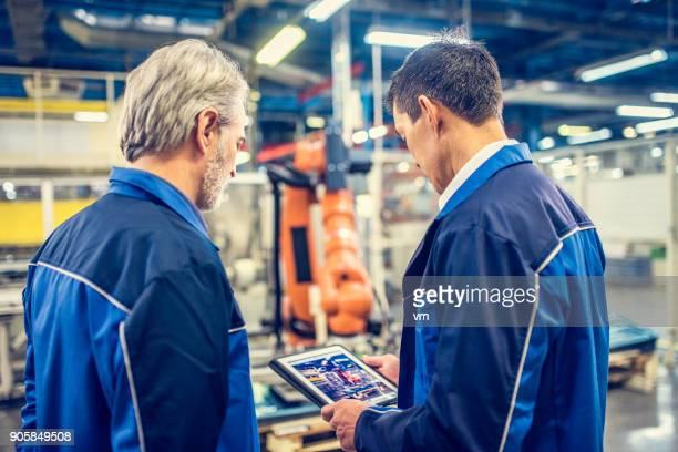 zwei ingenieure untersuchen roboterarm in fabrik - rechnerunterstützte fertigung stock-fotos und bilder