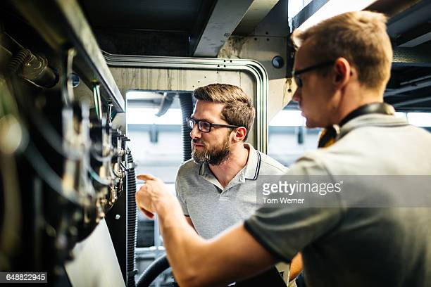 Two engineers in a printery checking a machine