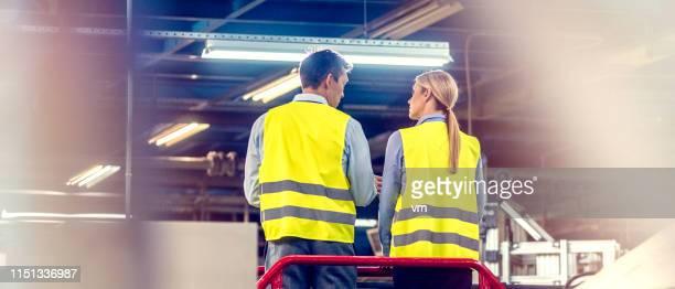 zwei ingenieure in automatisierter fabrik - verwaltungsbezirk meta stock-fotos und bilder