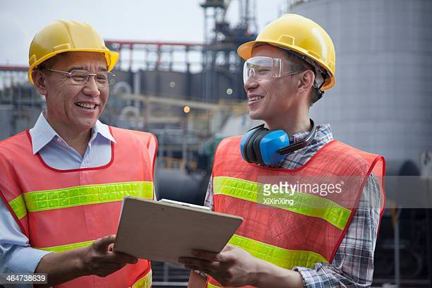 Two engineers in protective workwear standing and laughing outside of a factory