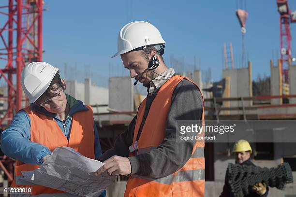 Two engineers looking at a blueprint at construction site, Freiburg Im Breisgau, Baden-Württemberg, Germany