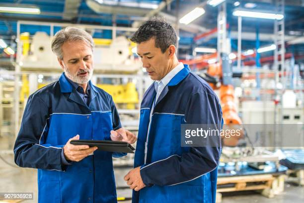 Two engineers looking at digital tablet near the production line