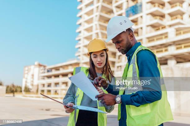 two engineers, male and female, in protective helmets and reflective clothing, standing on construction site infront of a large building. - civil engineering stock pictures, royalty-free photos & images