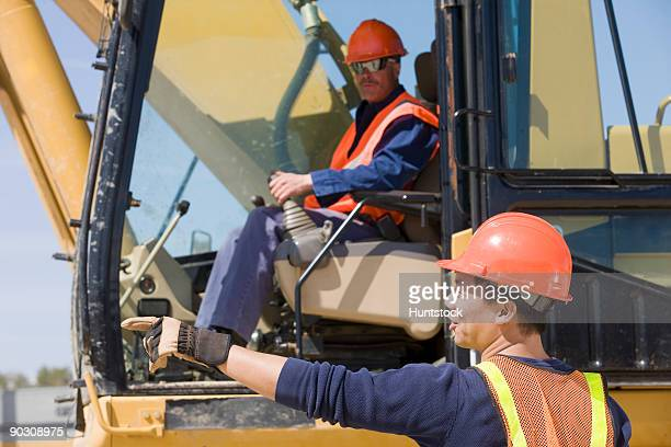 Two engineers operating an earth mover at a gravel and asphalt plant