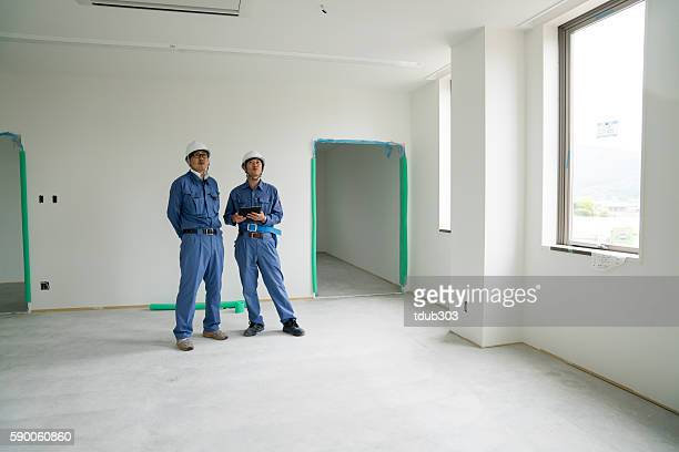 Two engineers or architects or inspectors at building construction site