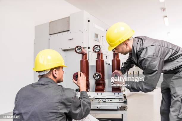 Two Engineers Repairing An Electric Transformer