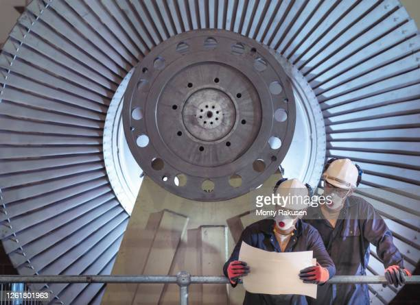 two engineers standing in front of low pressure steam turbines for electricity generation in turbine repair factory. - industry stock pictures, royalty-free photos & images