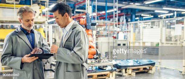 two engineers using digital tablet in a factory - electronics stock pictures, royalty-free photos & images