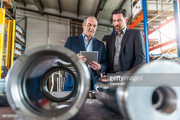 Two engineers with digital tablet in front of hydraulic cylinder