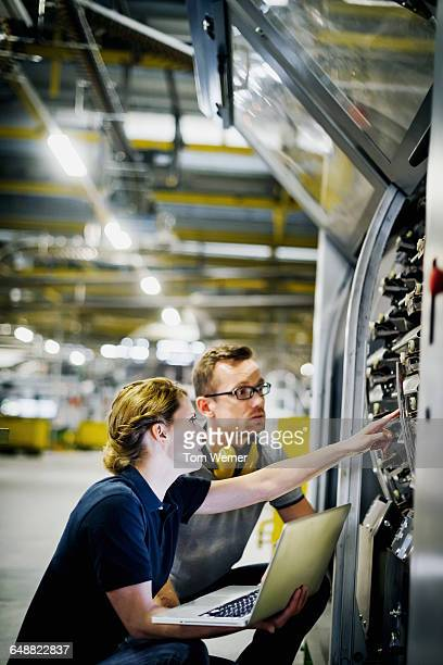 two engineers with laptop checking machine - leanincollection stock pictures, royalty-free photos & images