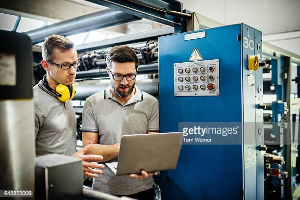 Two engineers with laptop in large printery