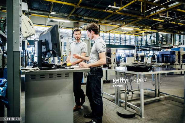 two engineers working at console together - industry stock pictures, royalty-free photos & images