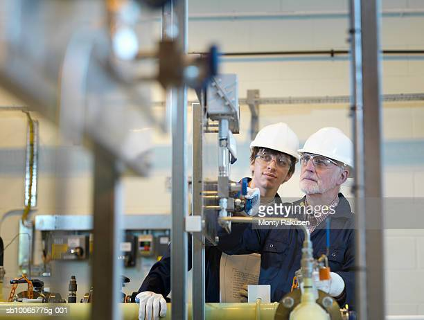 Two engineers working behind machinery