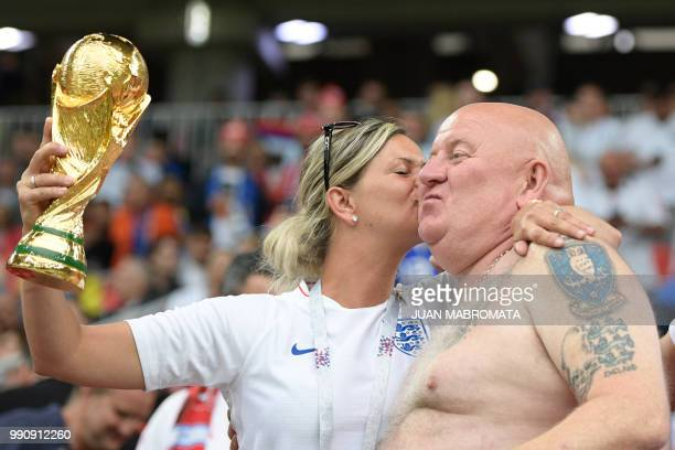 Two England fans hold a replica of the World Cup trophy before the Russia 2018 World Cup round of 16 football match between Colombia and England at...