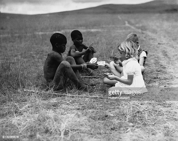 Two English children play cards with native children of Pondoland. | Location: Pondoland, South Africa.