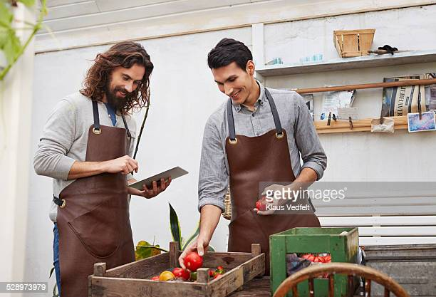 Two entrepreneur guys keeping track of vegetables