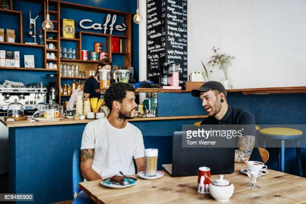 Two Entrepreneurs Discussing Business Plans At Cafe Together