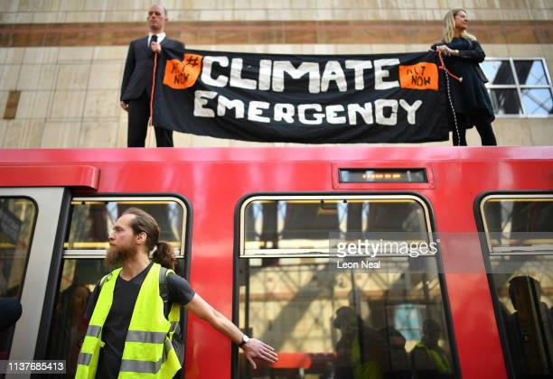 Two Environmental campaigners stand on top of a DLR train while a third campaigner stands by the doors below during the third day of a coordinated...