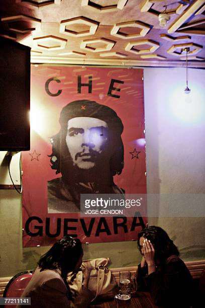 Two Ethiopian girls have a drink next to a poster of Argentinian revolutionary Ernesto Che Guevara 06 October 2007 at a 'Che Bar' in Addis Ababa Next...