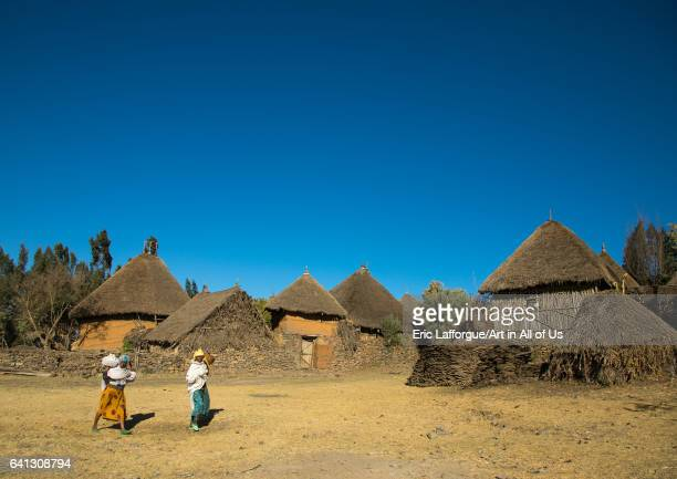 Two ethiopian women passing in front of stone houses village in the highlands on January 23 2017 in Debre Birhan Ethiopia