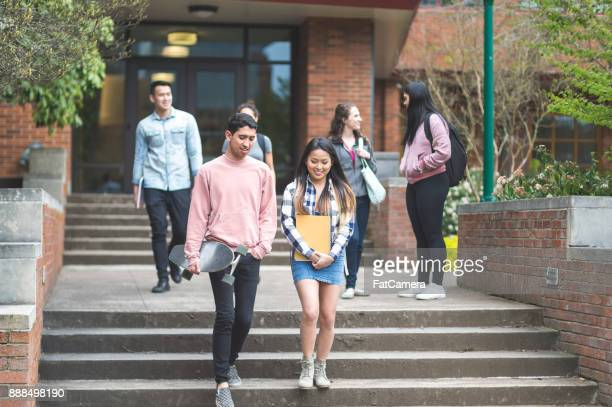 Two ethnic college friends leave class together and walk across campus.