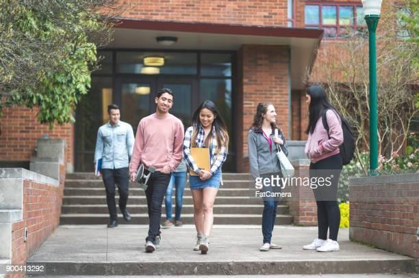 twee etnische college vrienden laat klasse samen en lopen over de campus. - nosotroscollection stockfoto's en -beelden