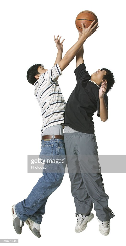 two ethnic teenage boys play basketball against each other : Foto de stock