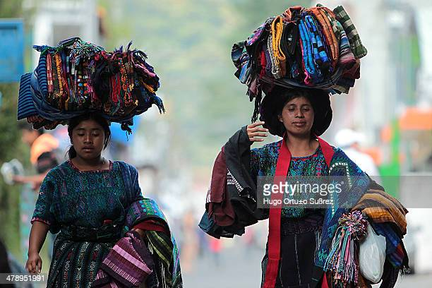 Two ethnic women carry handwoven cotton and wool handicrafts on their heads. Panajachel in the Guatemalan highlands at 1,500 meters above sea level,...