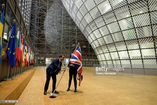 Two EU Officials remove the Union Jack flag from the atrium of the Europa building the EU Council headquarter on January 31 2020 in Brussels Belgium...