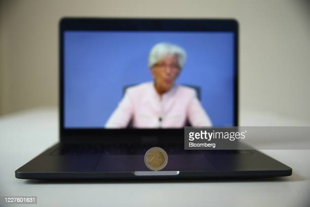 A two euro currency coin stands on a laptop displaying Christine Lagarde president of the European Central Bank during a live stream video of the...