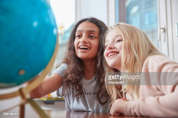 Two excited girls looking at globe
