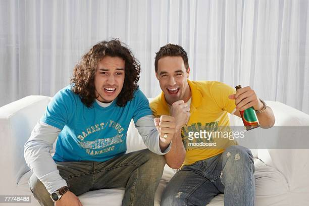 Two Excited Young Men Drinking and Watching Television