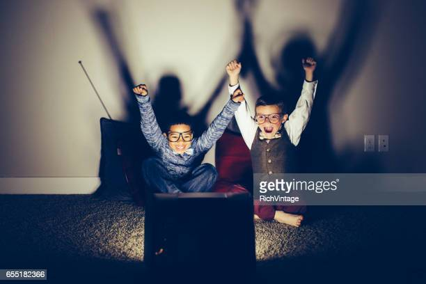 two excited young nerds watching sporting event on television - television show stock pictures, royalty-free photos & images