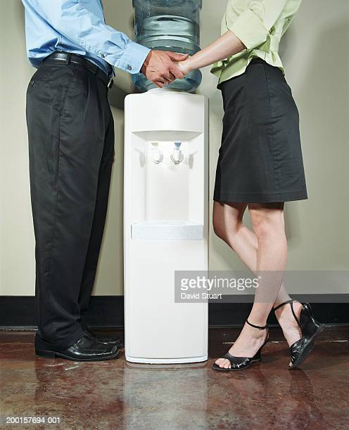 two executives holding hands by water cooler, low section, side view - work romance stock pictures, royalty-free photos & images