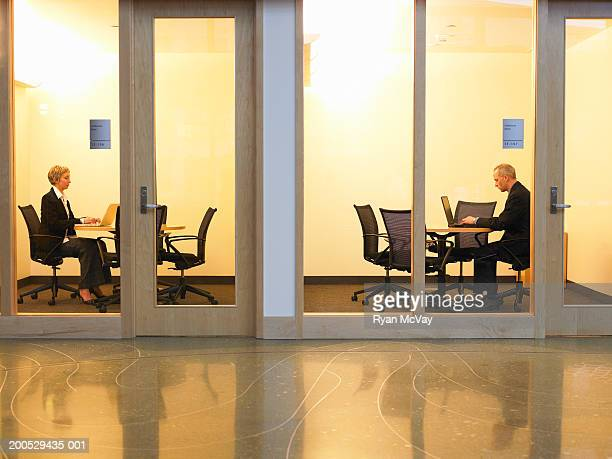 two executives using laptops in conference rooms, side view - hot desking photos et images de collection