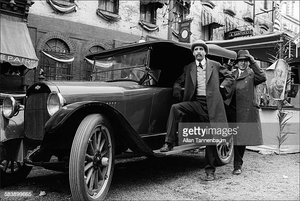 Two extras pose by an antique car on the East Village set of the film 'The Godfather Part II' New York New York March 10 1974