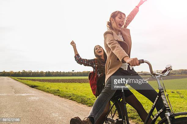 Two exuberant young women sharing a bicycle in rural landscape