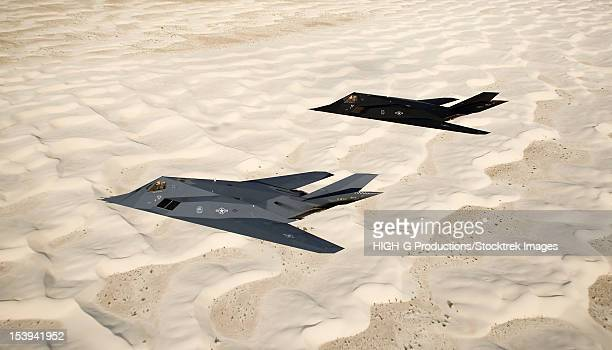 Two F-117 Nighthawk stealth fighters fly on a training sortie out of Holloman Air Force Base, New Mexico, over the White Sands National Monument.