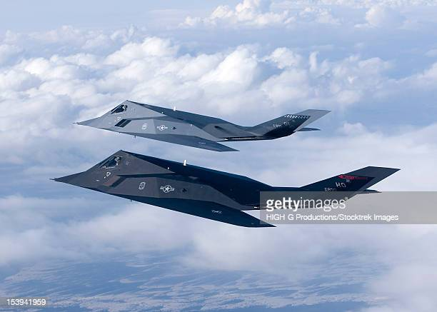 two f-117 nighthawk stealth fighters fly on a training sortie out of holloman air force base, new mexico. - stealth bomber stock photos and pictures