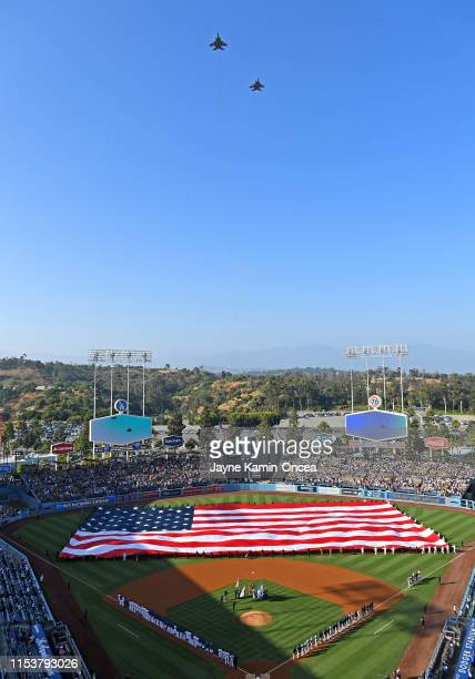 Two F15 Eagle fighter jets perform a fly over as members of the military hold an American Flag on the field during the National Anthem before the...