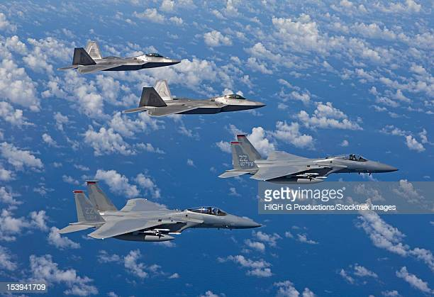 Two F-15 Eagles and F-22 Raptors fly in formation.